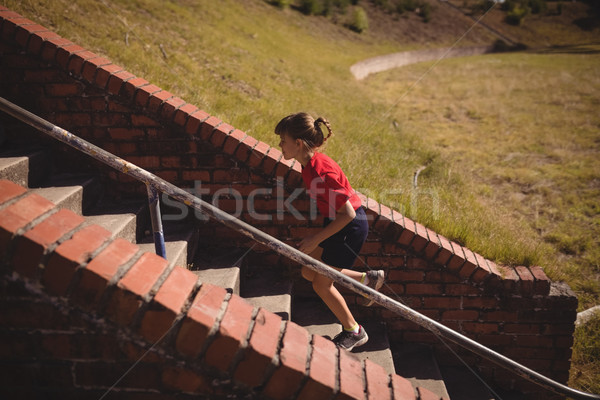 Determined girl running upstairs during obstacle course Stock photo © wavebreak_media