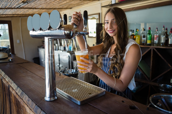 Portrait of young barmaid pouring beer from tap in glass Stock photo © wavebreak_media