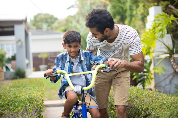Stock photo: Man assisting son cycling