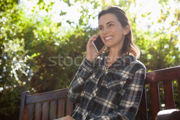 Low angle view of smiling beautiful woman talking on mobile phone while sitting on wooden bench Stock photo © wavebreak_media