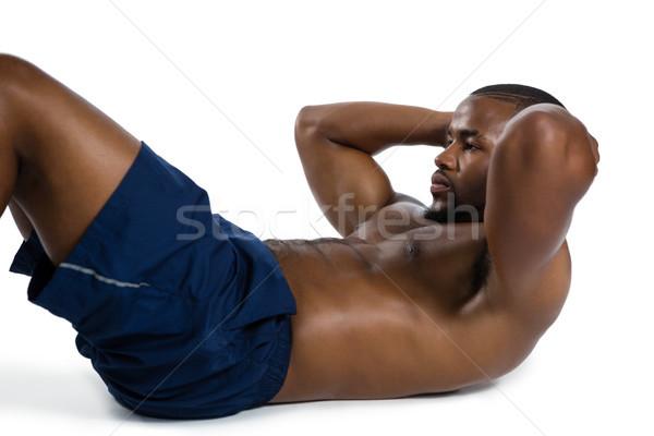 Shirtless male athlete practicing sit ups Stock photo © wavebreak_media