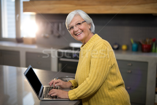 Glimlachend senior vrouw met behulp van laptop keuken portret Stockfoto © wavebreak_media