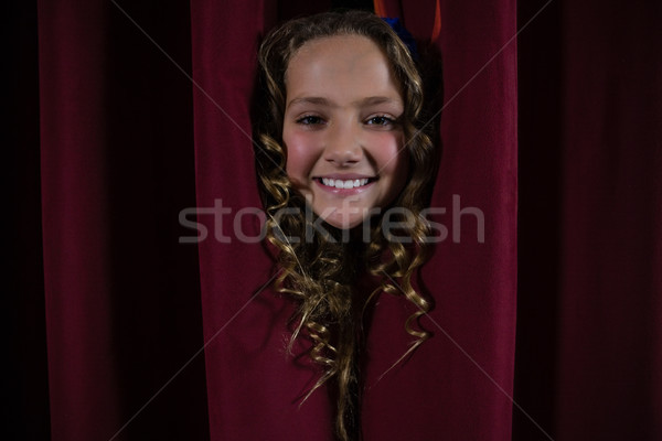 Portrait of smiling female artist peeking through the red curtain Stock photo © wavebreak_media