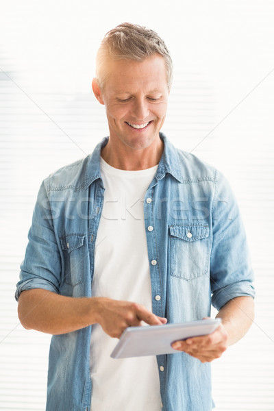 Smiling businessman scrolling on a tablet Stock photo © wavebreak_media