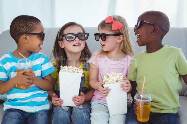 Happy kids enjoying popcorn and drinks while sitting Stock photo © wavebreak_media