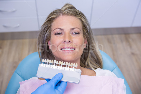 Dentist holding tooth whitening equipment by smiling patient at clinic Stock photo © wavebreak_media