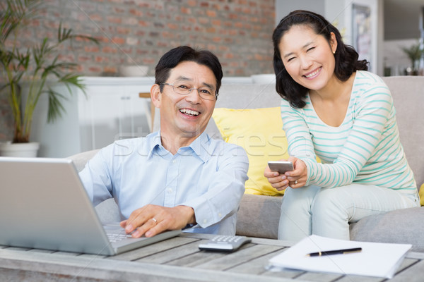 Stockfoto: Glimlachend · paar · met · behulp · van · laptop · smartphone · woonkamer · computer