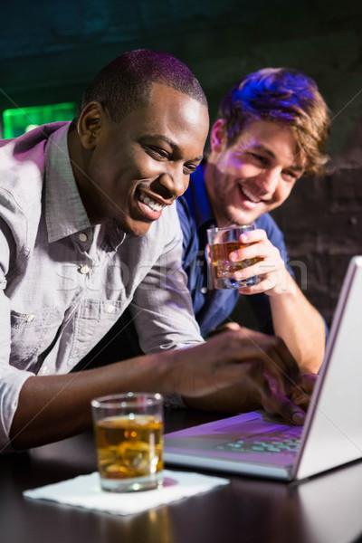 Dois homens uísque usando laptop bar contrariar computador Foto stock © wavebreak_media