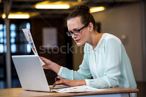 Foto stock: Mulher · olhando · traçar · usando · laptop · escritório · papel