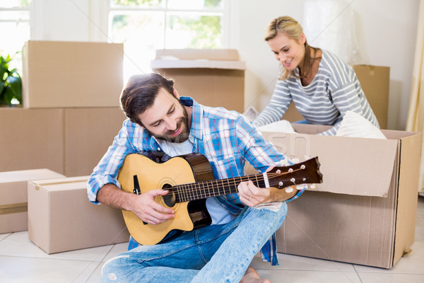 Man playing a guitar while woman unpackaging cardboard boxes in  Stock photo © wavebreak_media