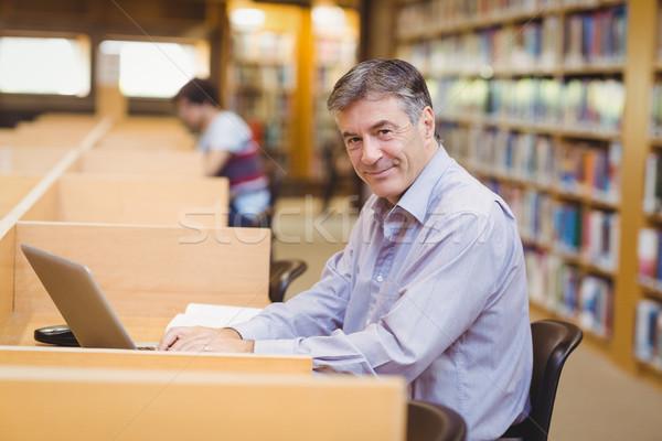 Ritratto felice professore seduta desk utilizzando il computer portatile Foto d'archivio © wavebreak_media