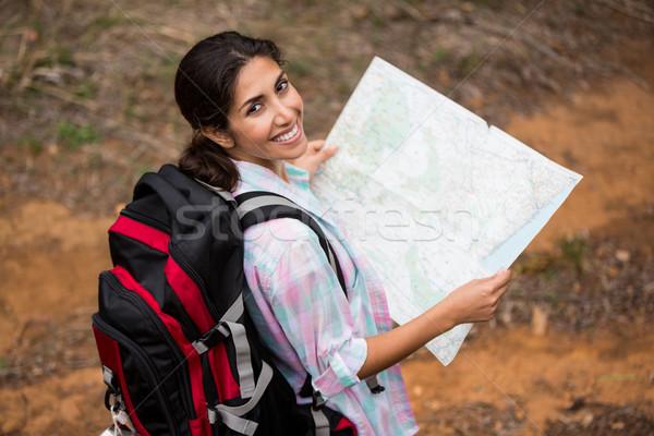 Mosolyog női természetjáró tart térkép erdő Stock fotó © wavebreak_media