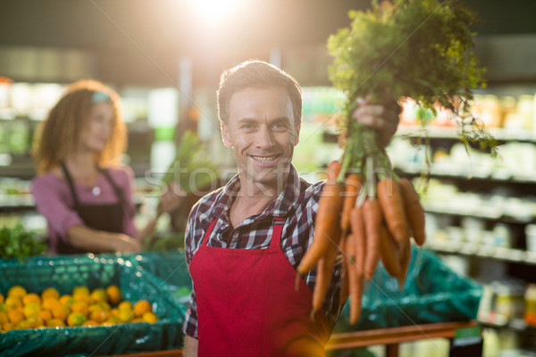 Smiling male staff holding bunch of carrots in organic section Stock photo © wavebreak_media