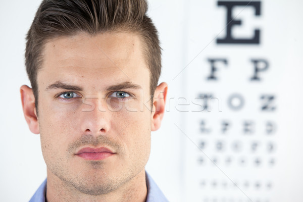 Man wearing contact lens with eye chart in background Stock photo © wavebreak_media