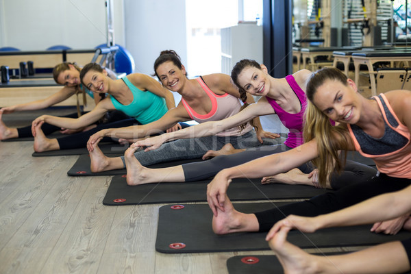 Women performing stretching exercise on exercise mat in gym Stock photo © wavebreak_media
