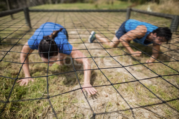 Fit man and woman crawling under the net during obstacle course Stock photo © wavebreak_media