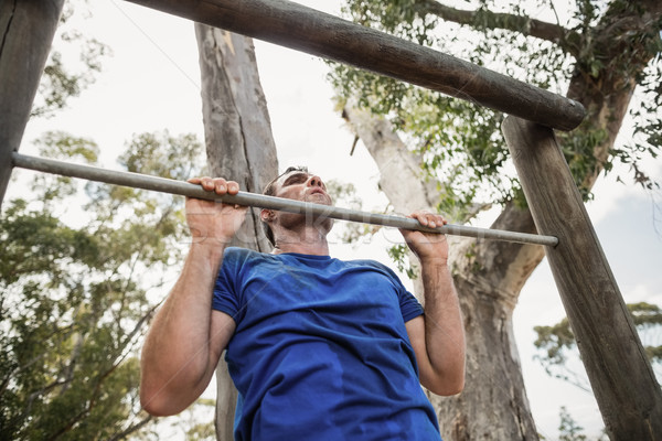 Fit man performing pull-ups on bar during obstacle course Stock photo © wavebreak_media