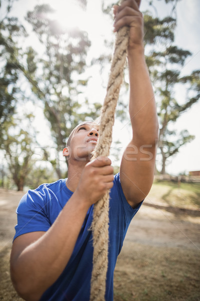 Fit man climbing rope during obstacle course Stock photo © wavebreak_media