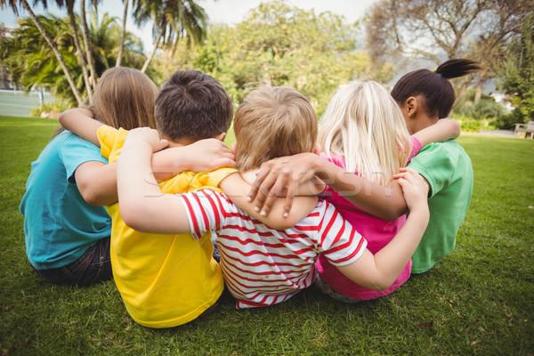 Mutlu sınıf arkadaşları oturma çim silah etrafında Stok fotoğraf © wavebreak_media