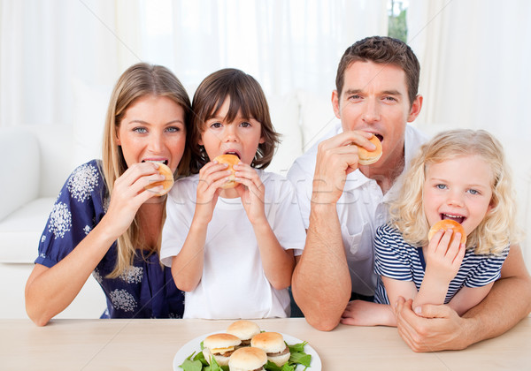 Hungry family eating burgers in the living room Stock photo © wavebreak_media