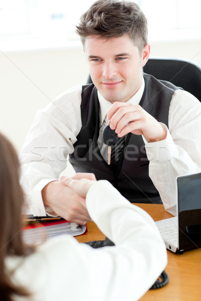 Young attractive salesman giving car's key to his customer sitting in his office Stock photo © wavebreak_media