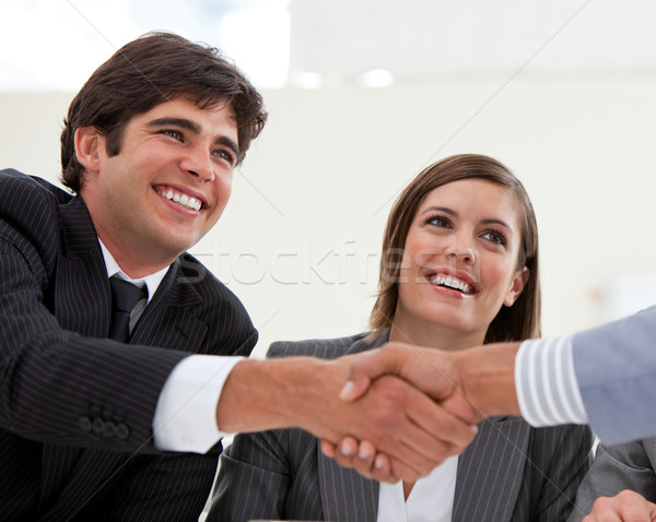 Smiling businessman and his colleague closing a deal with a partner in a meeting Stock photo © wavebreak_media