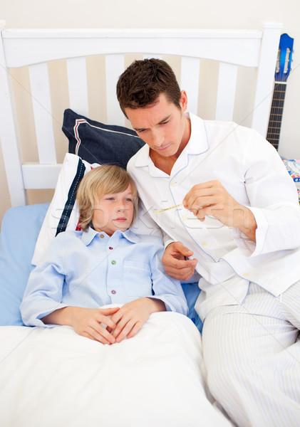 Attractive father checking his son's temperature in the bedroom Stock photo © wavebreak_media