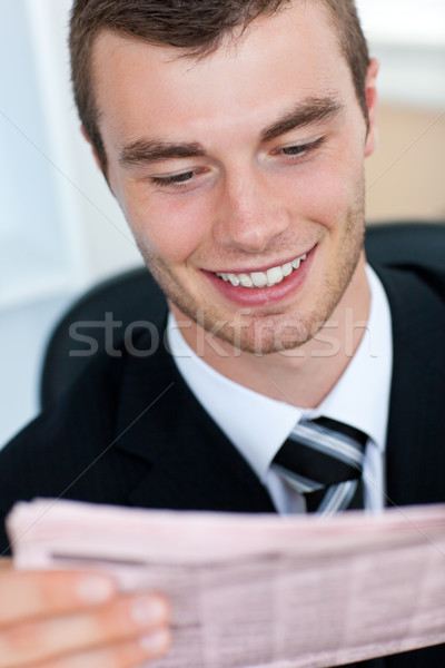 Stock photo: Radiant businessman reading newspaper in office