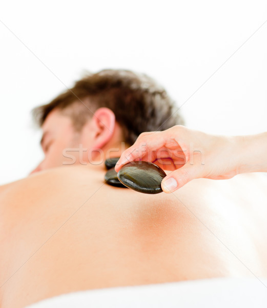 Stock photo: Close-up of a positive young man having a back massage with hot stone in a spa center