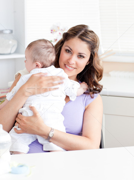 Positive young mother holding her baby in the kitchen at home Stock photo © wavebreak_media