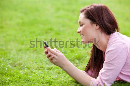 Attrative young pregnant woman lying on the grass texting  Stock photo © wavebreak_media