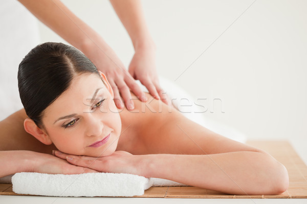 Pretty dark-haired woman enjoying a massage in a spa centre Stock photo © wavebreak_media