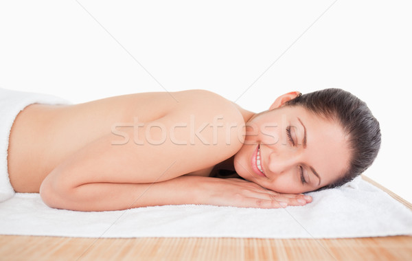 Smilling dark-haired young woman on a masage table closing her eyes Stock photo © wavebreak_media