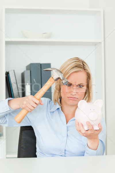 Angry woman wanting to destroy her piggy bank in her office Stock photo © wavebreak_media
