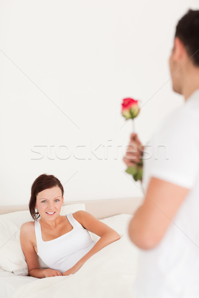 Young woman looking into camera when husband arrives with rose in her bedroom Stock photo © wavebreak_media
