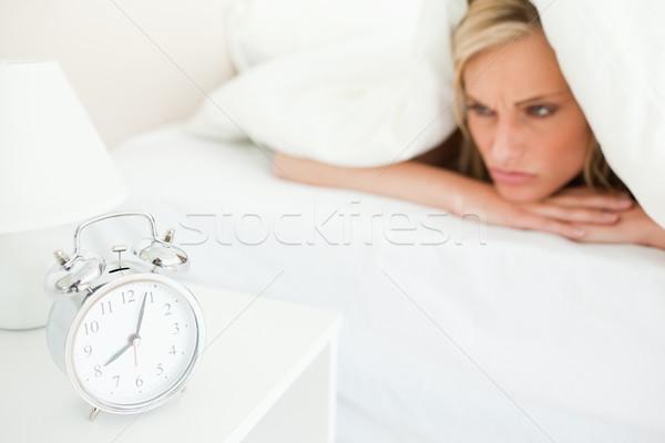 Displeased blonde woman waking up in hher bedroom Stock photo © wavebreak_media
