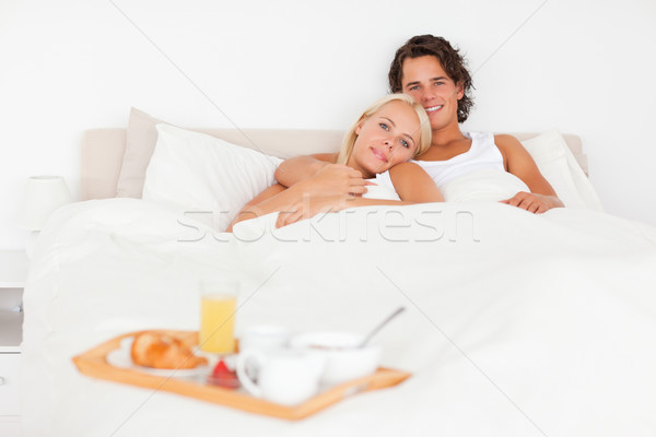 Smiling couple with the breakfast put on a tray with the camera focus on the models Stock photo © wavebreak_media