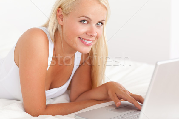 Close up of a woman with a laptop in her bedroom Stock photo © wavebreak_media