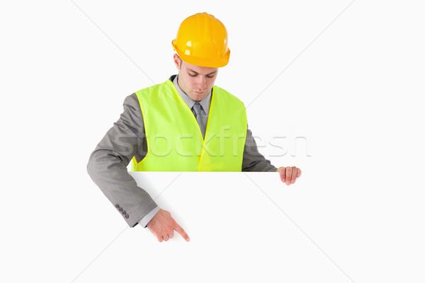 Builder pointing at something against a white background Stock photo © wavebreak_media