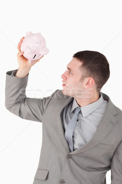 Portrait of a businessman looking in a piggy bank against a white background Stock photo © wavebreak_media