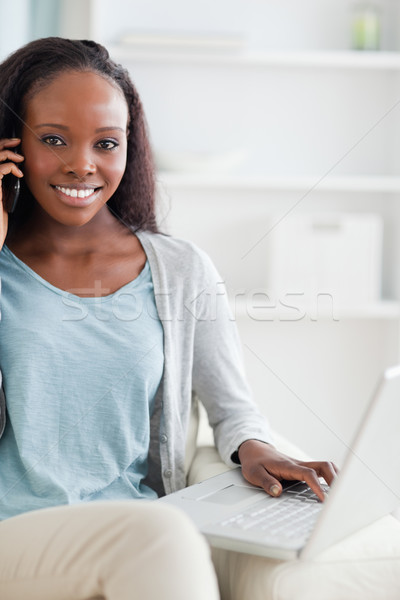 Close up of smiling woman with cellphone and laptop on sofa Stock photo © wavebreak_media