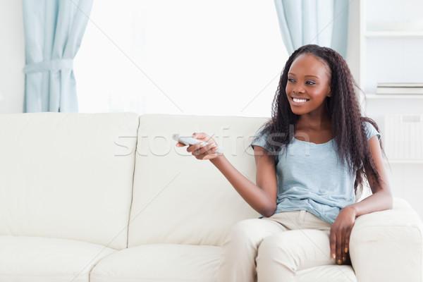 Smiling woman on sofa changing TV programme Stock photo © wavebreak_media