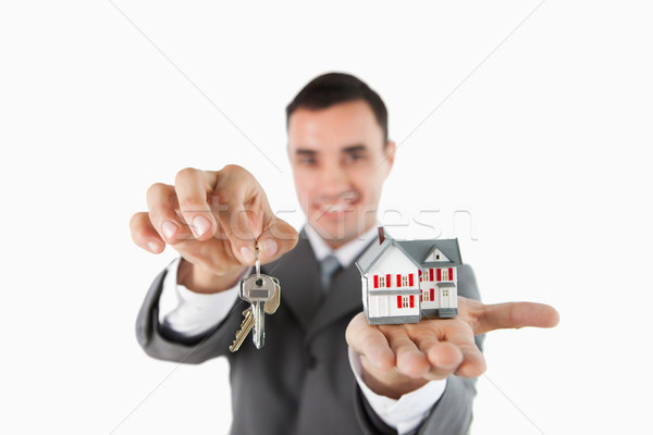 Close up of keys and miniature house being held by male estate agent against a white background Stock photo © wavebreak_media