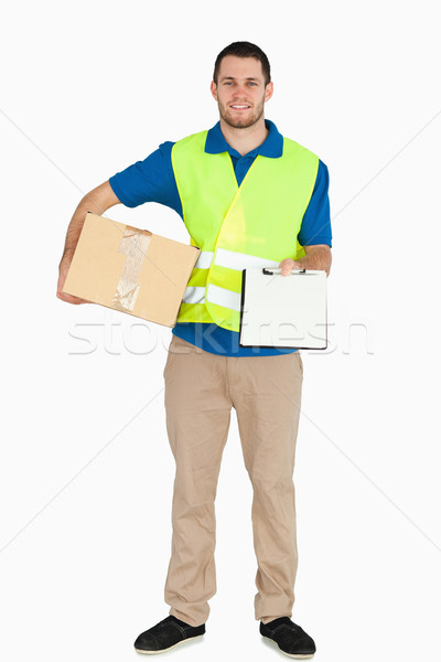 Smiling young delivery man asking for signature against a white background Stock photo © wavebreak_media