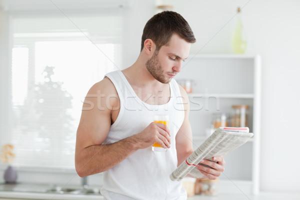 Man drinking orange juice while reading the news in his kitchen Stock photo © wavebreak_media