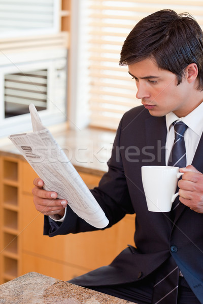 Portrait of a businessman drinking tea while reading the news in his kitchen Stock photo © wavebreak_media