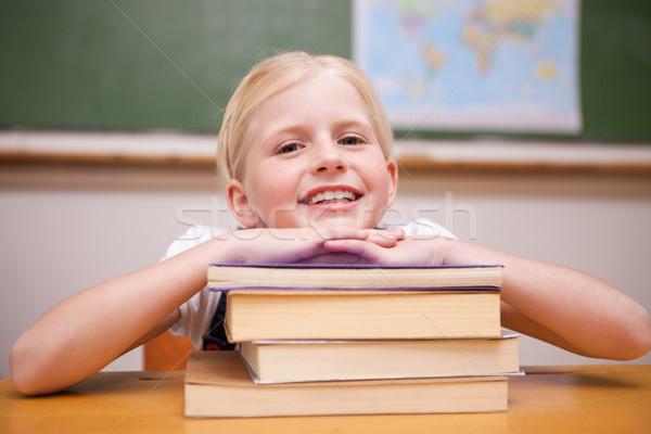 Girl leaning on books in a classroom Stock photo © wavebreak_media