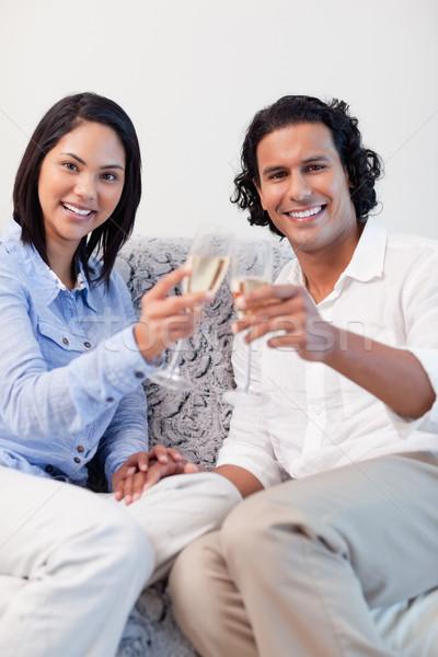 Happy young couple drinking sparkling wine on the sofa Stock photo © wavebreak_media