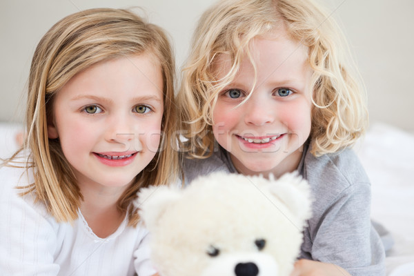 Siblings lying on the bed together with their teddy Stock photo © wavebreak_media