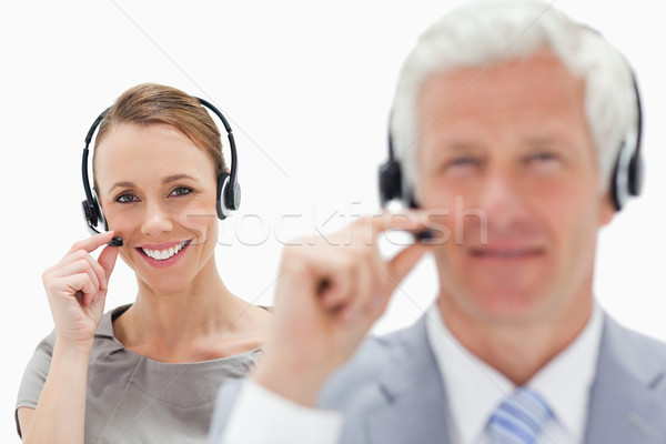 Close-up of a smiling woman talking in background with a white hair man while wearing a headset agai Stock photo © wavebreak_media